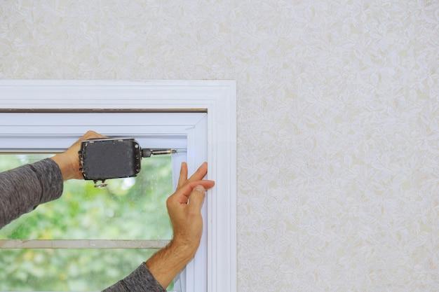 Строитель устанавливает новое окно в доме с помощью отвертки