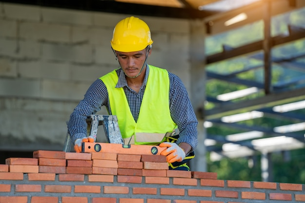 Construction worker installing red brick with trowel putty knife for new house building at construction site