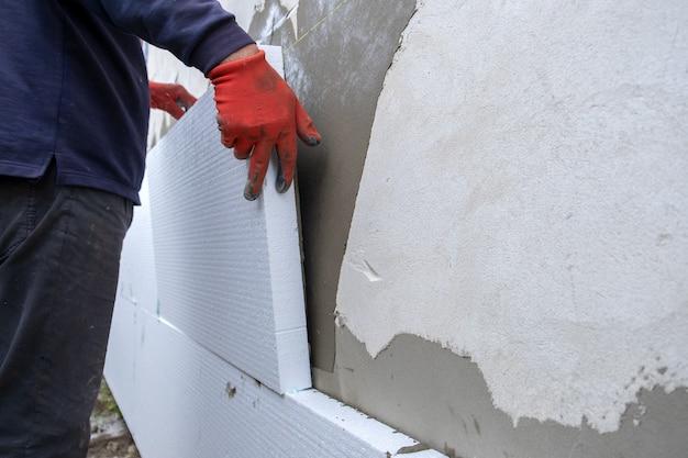 Строитель устанавливает изоляционные листы из пенополистирола на стене фасада дома для тепловой защиты.