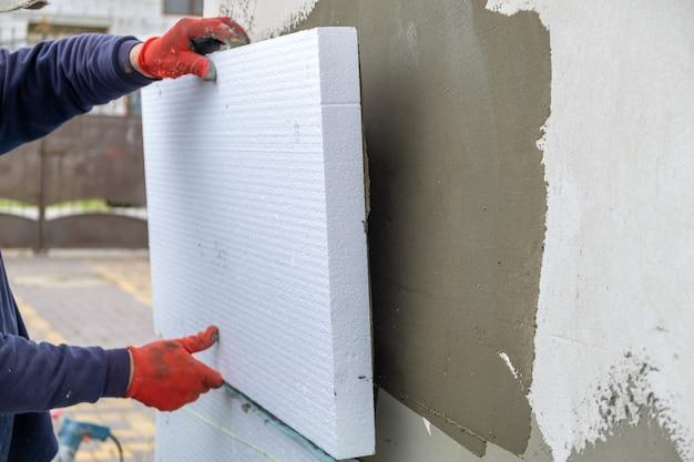 Строитель устанавливает изоляционные листы из пенополистирола на стене фасада дома