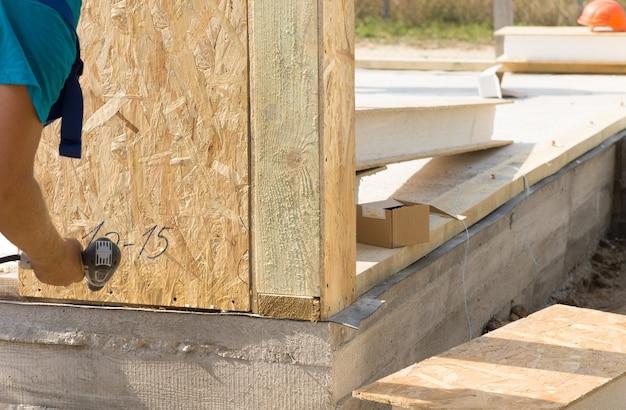 건설 노동자가 새 건물에 벽 단열재를 설치하고 손을 닫고 새로 깔린 시멘트 바닥 모서리를 닫습니다.