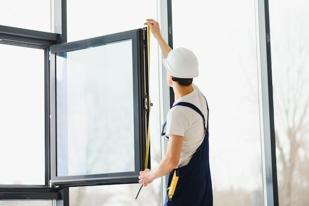 Строитель устанавливает окно в доме