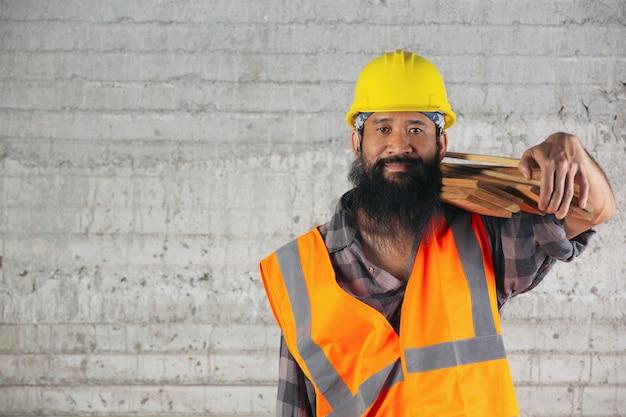 Строительный рабочий очень тяжело несет деревянные доски на строительной площадке.