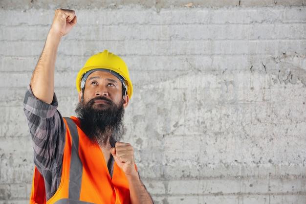 建設労働者が中に立って、建設現場での仕事のための戦いを感じています。