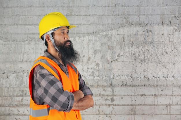 L'operaio edile è in piedi dentro e sente la lotta per il lavoro in cantiere.