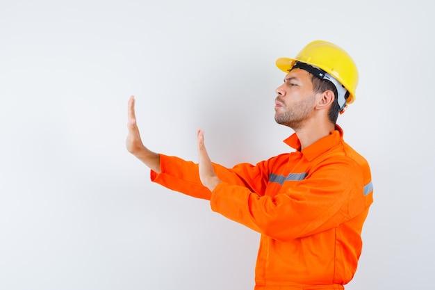 Operaio edile che tiene le mani per difendersi in uniforme, casco e sguardo infastidito.