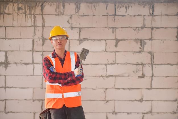 Строитель кладет кирпичи и строит барбекю на промышленной площадке