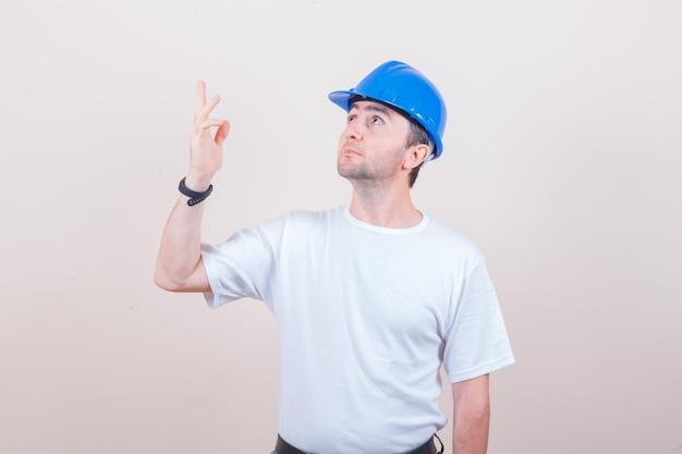 Строитель смотрит вверх, поднимает руку в футболке, шлеме и выглядит сосредоточенным