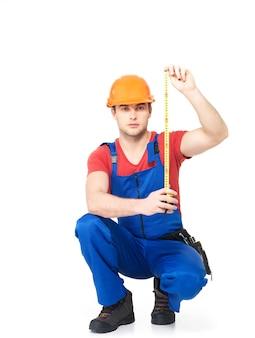 흰색 벽을 측정하는 건설 노동자
