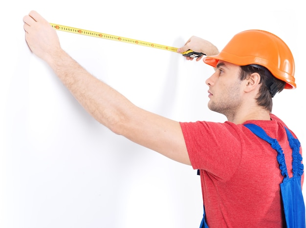 Construction worker measuring the wall on white