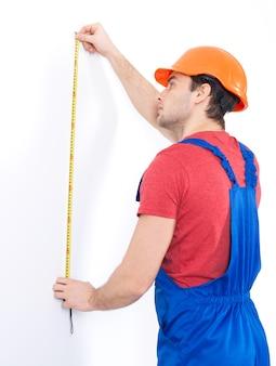 Operaio edile che misura il muro su bianco