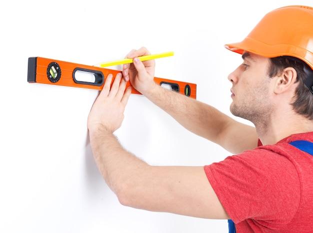 Строительный рабочий, измерения с уровнем на стене на белом