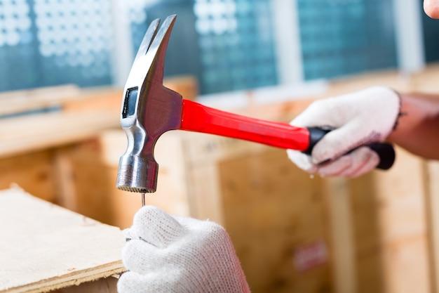 Строитель на строительной площадке закрывает деревянный ящик или грузовой контейнер молотком и гвоздем