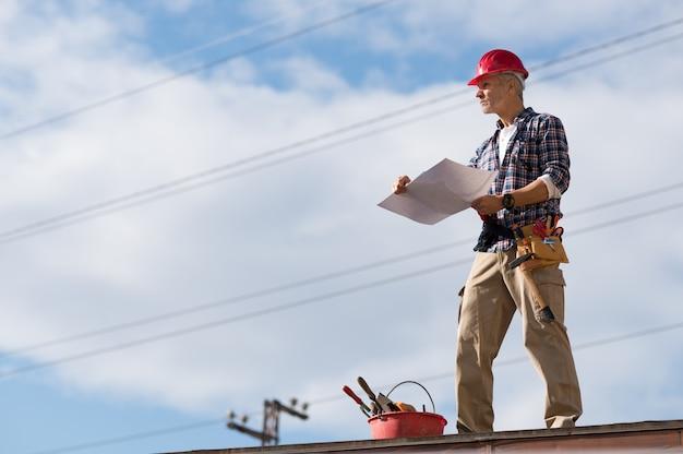 Строительный рабочий на крыше
