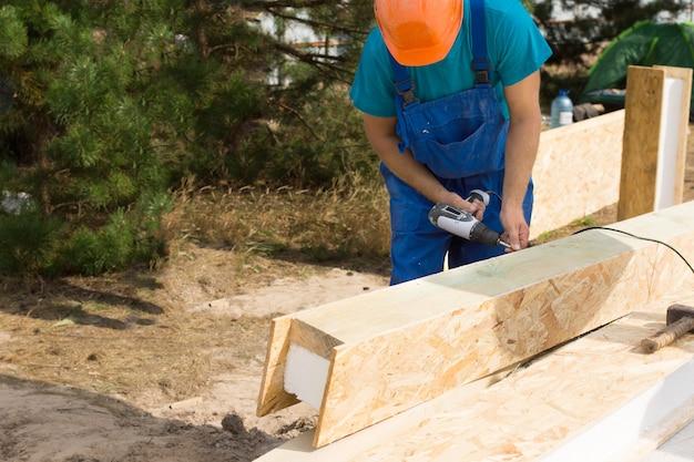 건설 노동자 또는 목수가 건축 현장의 나무 그늘에 서서 나무 패널과 내부 단열재로 빔을 드릴링합니다.