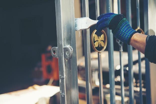 Строитель красит забор дома