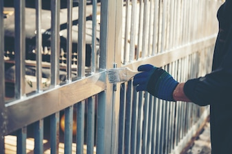 Construction worker painting fence at home