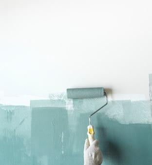 Строитель красит стену