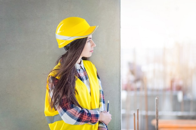 Construction worker pensive girl. young female engineer looking at a construction site