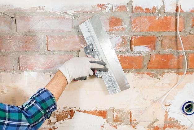 집을 리노베이션하는 동안 주걱으로 벽돌 벽을 석고 건설 노동자