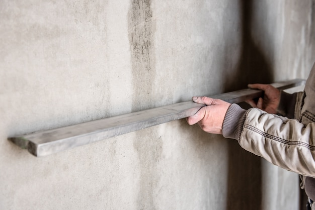 Construction worker plastering a wall with leveler