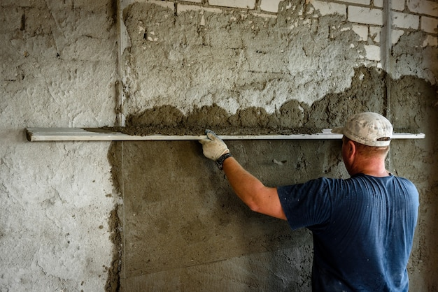 Construction worker plastering wall with leveler.