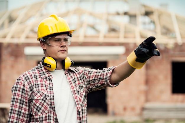 Строительный рабочий, указывая на что-то