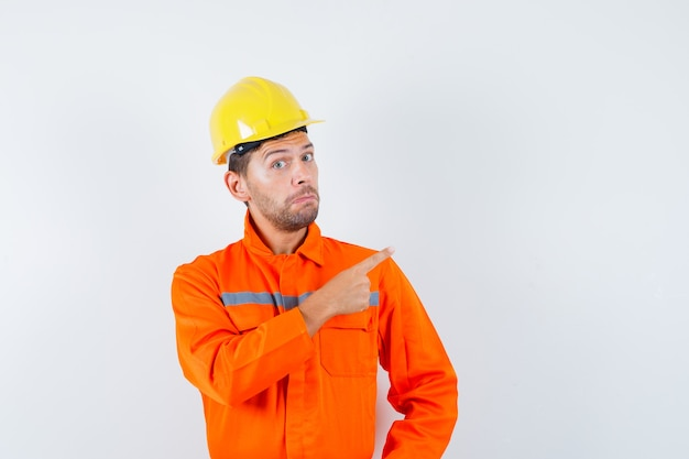 Construction worker pointing away in uniform, helmet and looking hesitant , front view.