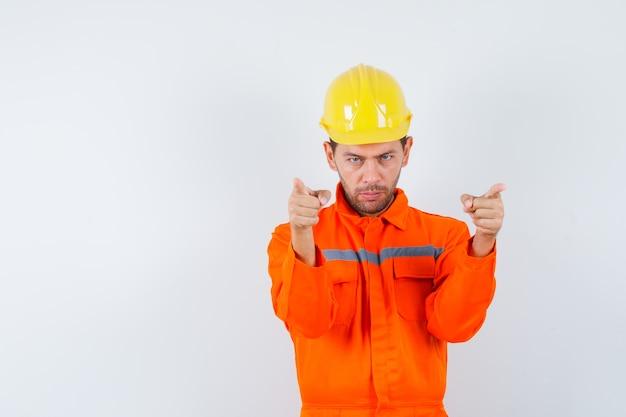 Operaio edile che indica in uniforme, casco e che sembra fiducioso. vista frontale.