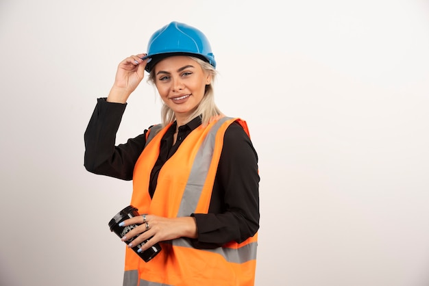 Construction worker posing with cup of tea on white background. high quality photo