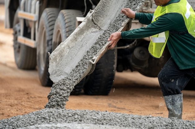 A construction worker pouring a wet concret at road construction site