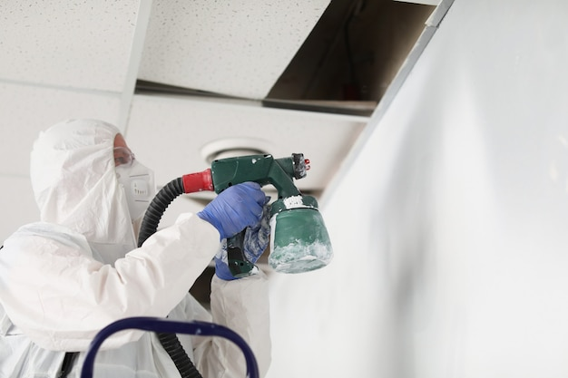 Construction worker in protective suit and respirator painting wall with spray gun
