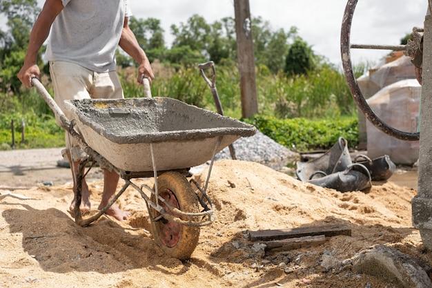Строитель тащит тачку. готовый цемент в тачке. оборудование машины смесителя цемента в строительной площадке.