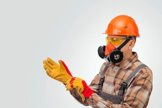 Рабочий-строитель надевает защитные перчатки на сером фоне. средства личной безопасности.