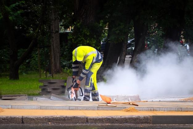 Строитель пилит кирпич на улице с облаком пыли позади.
