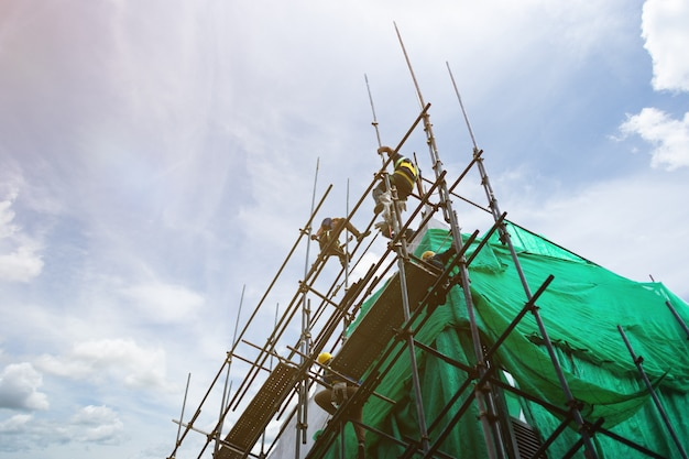 Construction worker on scaffold, with sky background.