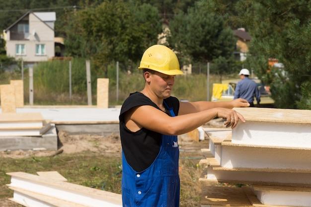건설 현장의 자재 더미에서 건설 현장의 벽용 단열 패널을 선택하는 건설 노동자 프리미엄 사진