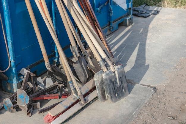 Строительные лопаты, щетки и инструменты, сложенные после работы. ручной строительный инструмент.