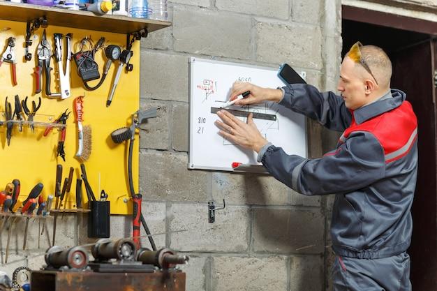 드로잉 보드에 청사진을 스케치하는 건설 노동자
