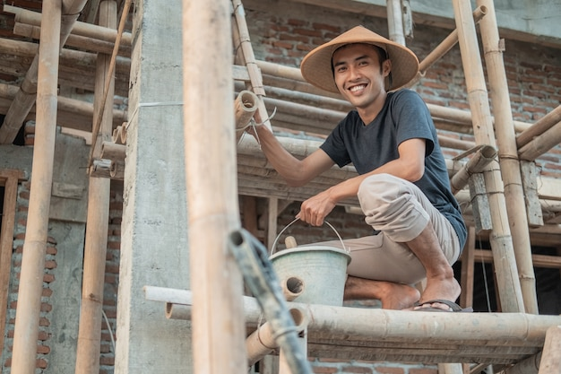Construction worker smile at the camera as he squat on the bamboo planks