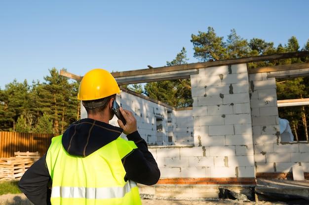 건설 노동자는 주택 건설의 배경에 대해 노란색 안전모와 반사 조끼를 입은 스마트폰으로 이야기합니다. 벽과 창문 개구부는 다공성 콘크리트 블록으로 만들어집니다.