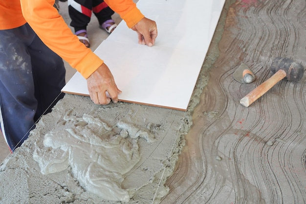 Construction worker tiler is tiling