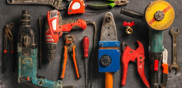 Инструменты рабочий-строителя на темном взгляд сверху предпосылки. реконструировать концепцию