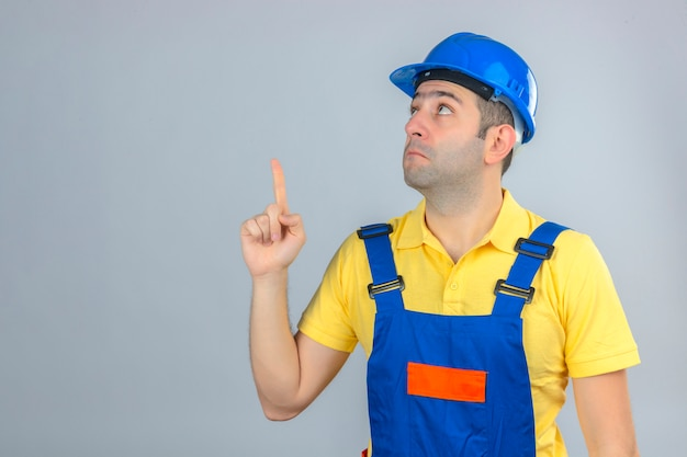 Construction worker in uniform and blue safety helmet surprised looking up and pointing up with finger isolated on white