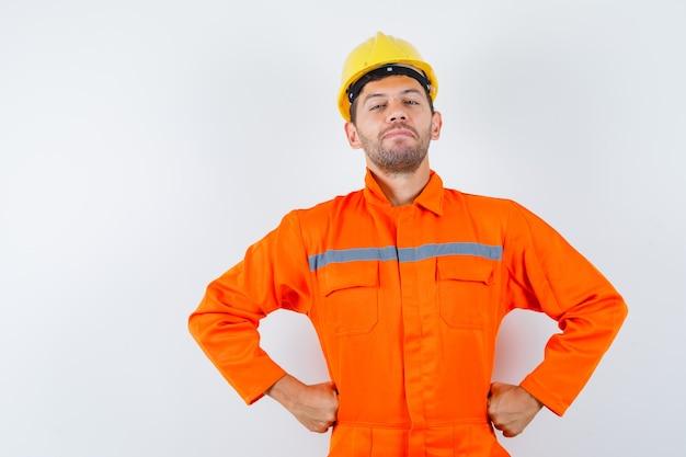 Operaio edile in uniforme, casco tenendo le mani sulla vita e guardando fiducioso, vista frontale.