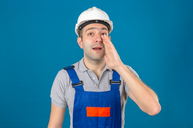 Construction worker in uniform and safety helmet yelling something and keeping hands near his opened mouth on blue isolated