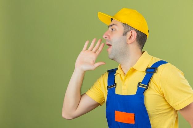Muratore in uniforme e cappuccio giallo che urla qualcosa e che tiene le mani vicino alla sua bocca aperta isolata su verde