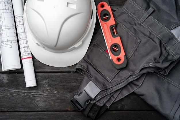 건설 노동자 unifrom, hardhat 및 나무 배경에 청사진