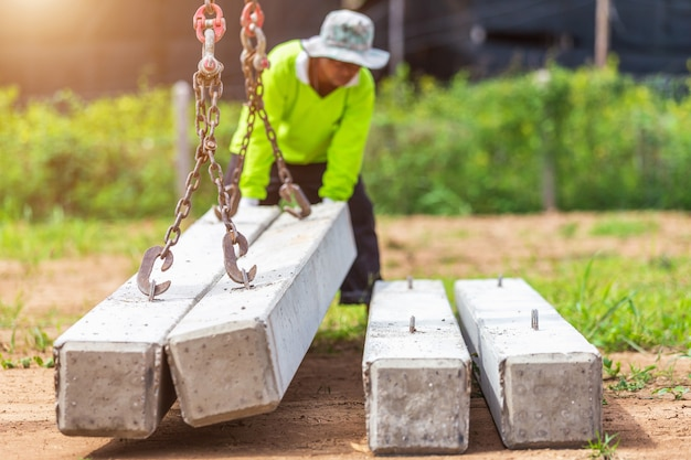 Construction worker unloading concrete stake from truck
