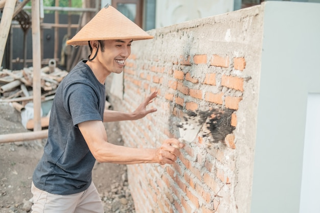 Construction worker use scoops to attach cement to the bricks